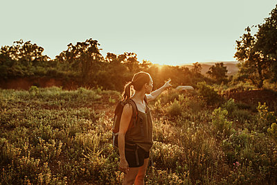 Woman pointing towards sunset while standing in forest - p300m2214060 by David Molina Grande