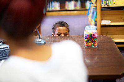 Boy in library peeking at candy jar - p300m980896f by zerocreatives