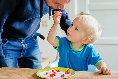 Little boy and his father eating red currants - p606m2178639 by Iris Friedrich