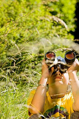 Boy looking through binoculars - p7610028 by Adeleida