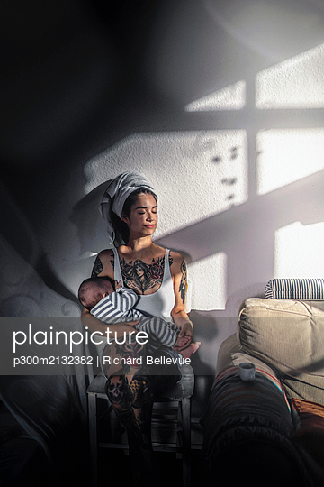 Tattooed young woman holding her baby at home enjoying the sunshine - p300m2132382 by Richárd Bellevue