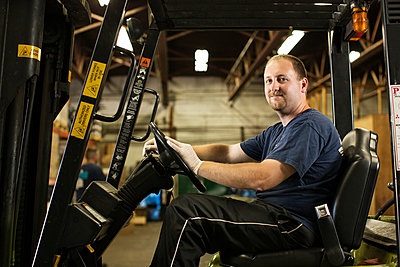 Portrait of mechanic sitting on forklift in workshop - p1166m995300f by Cavan Images