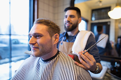 Barber with scissors behind male client in barbershop - p1192m1231177 by Hero Images
