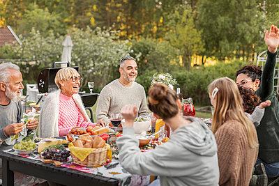 Family having meal in garden - p312m2208238 by Plattform