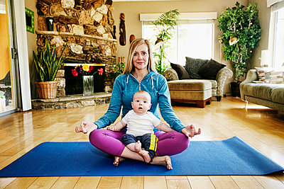 Mother meditating on exercise mat with baby in lap - p555m1305277 by Peathegee Inc