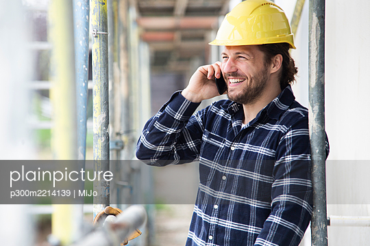 Construction worker talking over smart phone while standing by scaffold at construction site - p300m2214139 by MiJo