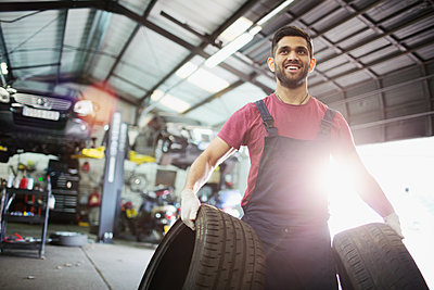 Portrait smiling male mechanic carrying tires in auto repair shop - p1023m2196727 by Tom Merton