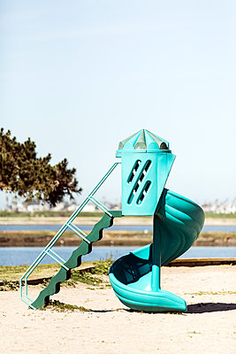 Turquoise slide on sand at playground against clear sky - p1094m1467637 by Patrick Strattner