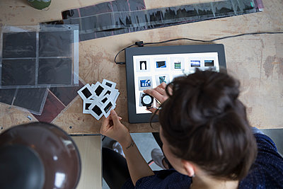 View from above female photographer reviewing photographic slides with lens magnifying loupe in art studio - p1192m1490271 by Hero Images
