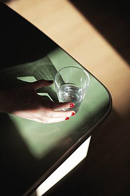 Hand greift nach Wasserglas - p1340m2008461 von Christoph Lodewick