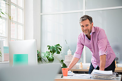 Portrait of a man working at desk in office - p300m2012521 by Florian Küttler