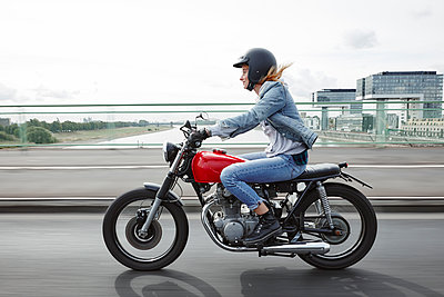 Germany, Cologne, young woman riding motorcycle on bridge - p300m2062601 by Rainer Holz