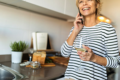 Happy mature woman drinking wine and talking on the phone in kitchen at home - p300m2144796 by Valentina Barreto
