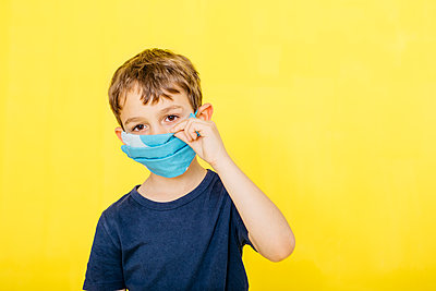 Portrait of cute boy adjusting face mask against yellow background - p300m2199137 by Josep Rovirosa