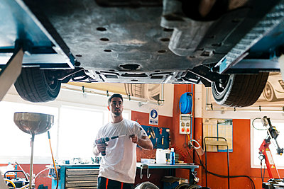 Young mechanic holding work tool looking at car while standing in auto repair shop - p300m2220692 by Ezequiel Giménez
