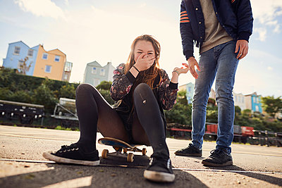 Two friends fooling around outdoors, young woman sitting on skateboard, laughing, low section, Bristol, UK - p429m1407900 by Matt Lincoln