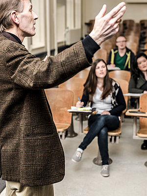 Teacher talking to students in classroom - p555m1479721 by Adam Crowley