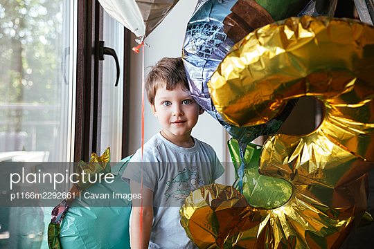 Cheerful birthday boy stands near the window - p1166m2292661 by Cavan Images