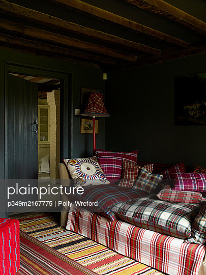 Cushions covered in assorted tartans on sofa in beamed farmhouse - p349m2167775 by Polly Wreford