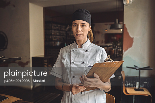 Portrait of chef with clipboard standing in restaurant - p426m2212096 by Maskot