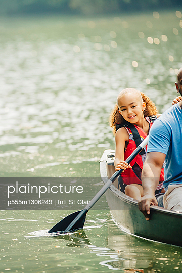 Father and daughter rowing canoe in lake - p555m1306249 by Inti St Clair photography