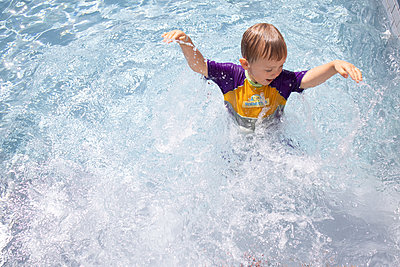 Little boy splashing about in swimming pool - p1640m2254805 by Holly & John