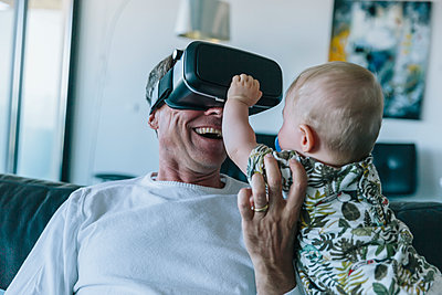 Happy man with baby wearing VR glasses - p300m1536186 by Mareen Fischinger