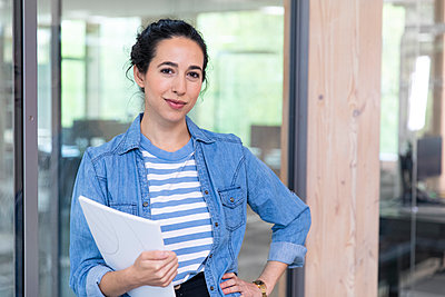 Confident female entrepreneur with hand on hip holding document while leaning on glass wall at office - p300m2265185 by Florian Küttler