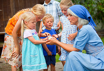Germany, Bavaria, Farm woman with children holding baby chick - p300m752389f by hsimages