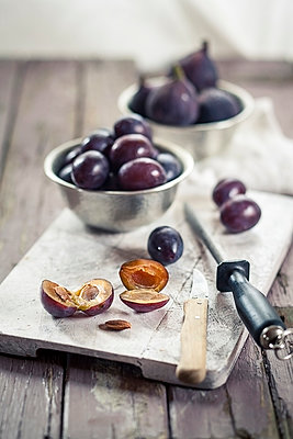 Pitting plums for making jam - p300m975374f by Susan Brooks-Dammann