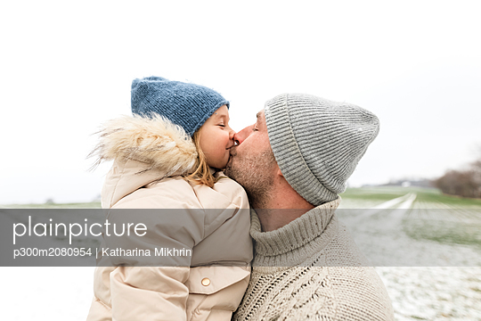 Father kissing daughter in winter - p300m2080954 by Katharina Mikhrin