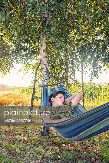 Boy lying in hammock - p879m2257746 by nico