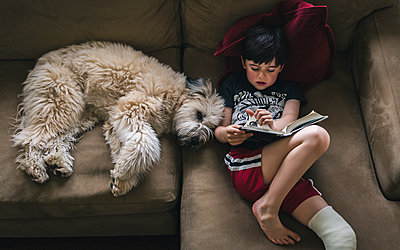 High angle view of boy with fractured leg reading book while lying by dog on sofa at home - p1166m2011868 by Cavan Images