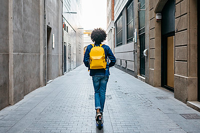Back view of young man with yellow backpack on E-Scooter in the city, Barcelona, Spain - p300m2114500 by Josep Rovirosa