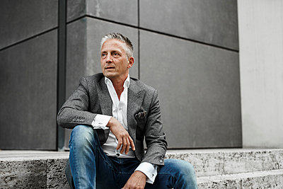Thoughtful businessman looking away while sitting on staircase - p300m2277452 by Sandro Jödicke