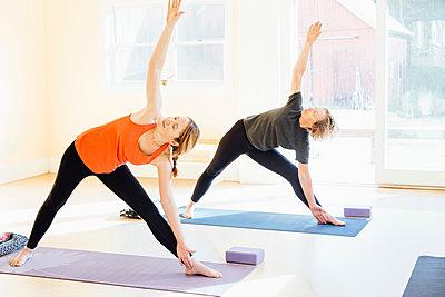 Two women practicing  triangle yoga pose (trikonasana) in yoga studio - p429m1578386 by Ashley Corbin-Teich