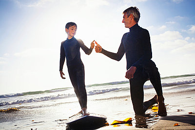 Father and son with surfboard on beach - p429m884151 by Yew! Images