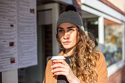 Young woman with coffee to go in the sunshine - p975m2222129 by Hayden Verry