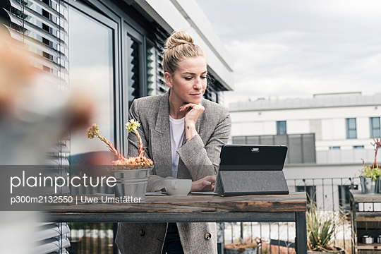Businesswoman using tablet on roof terrace - p300m2132550 by Uwe Umstätter