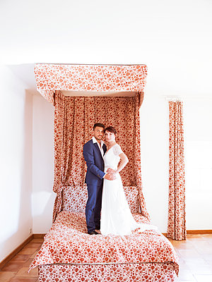 Bride and groom on bed - p1105m2126397 by Virginie Plauchut
