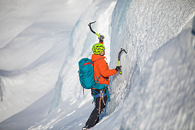 Ice climber swings his ice axe into a glacial serac while climbing. - p1166m2124318 by Cavan Images