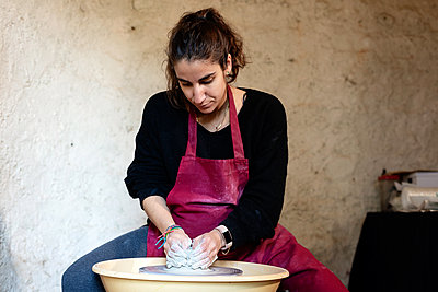 Ceramist artist female working in her atelier with The Pottery Wheel - p1166m2194104 by Cavan Images