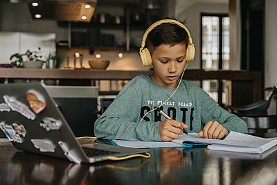 Schoolboy learning at home, using laptop and headphones - p300m2214059 by Mareen Fischinger