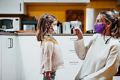 Mother wearing face mask checking temperature of daughter while sitting at home - p300m2225360 by Eva Blanco