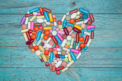 Tablets, pills and capsules shaped like a heart on blue wood - p300m965196f by Ophelia