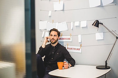 Creative businessman talking on mobile phone while sitting at desk in office - p426m2033172 by Maskot