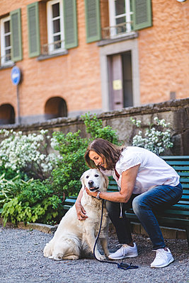 Full length of senior woman embracing dog while sitting on bench at park - p426m2046371 by Maskot