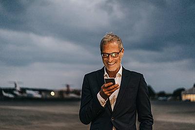Reifer Geschäftsmann liest eine Kurznachricht - p586m1208649 von Kniel Synnatzschke