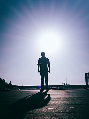 Rear view silhouette of man walking away  - p794m1510967 by Mohamad Itani