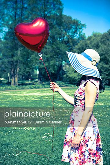 Frau hält Herzluftballon - p045m1154672 von Jasmin Sander